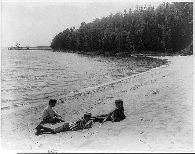 Three boys lounging on beach, Adirondacks