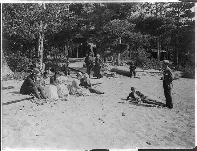 People relaxing on sandy beach in the Adirondack Mts., N.Y.