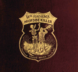 An embossed gold shield featuring a man threatening a skeleton with a weapon labeled Microbe Killer.