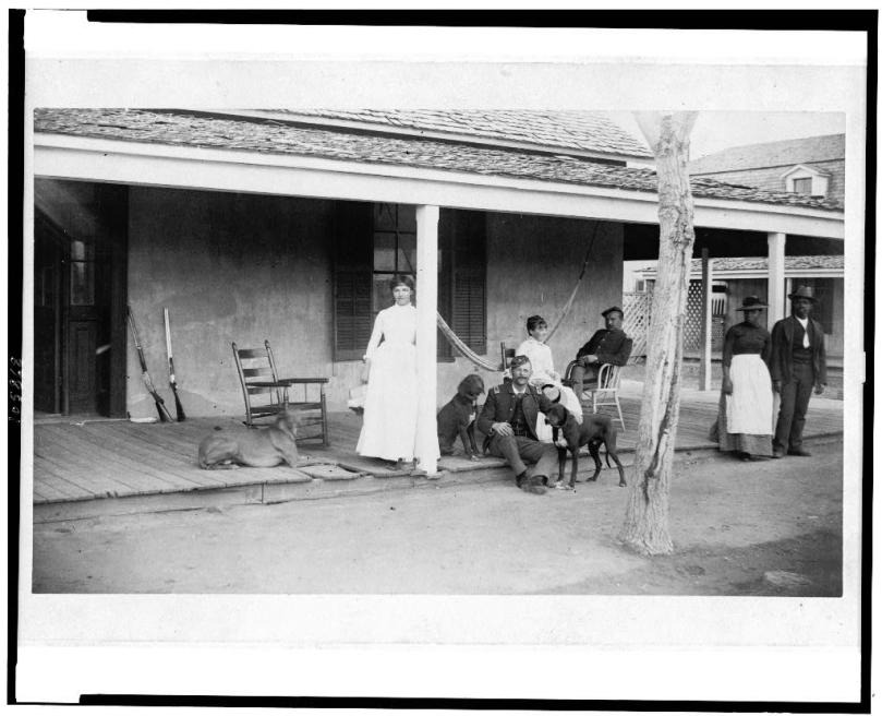 Two soldiers and two women on porch, with Afro-American woman and man to right, Fort Verde, Arizona