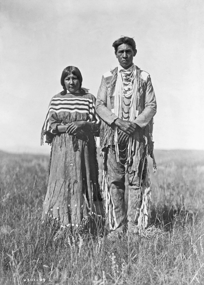 Edward S. Curtis - Piegan man and woman standing in open prairie